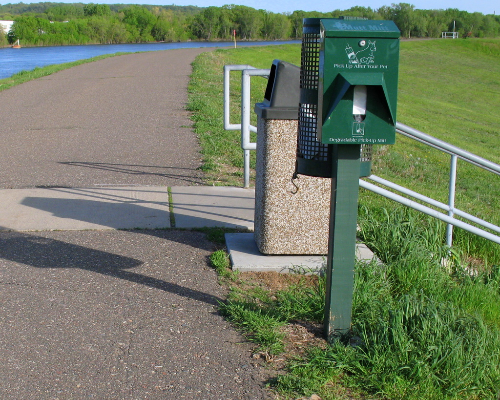the poop removal dispenser machine on a walking path