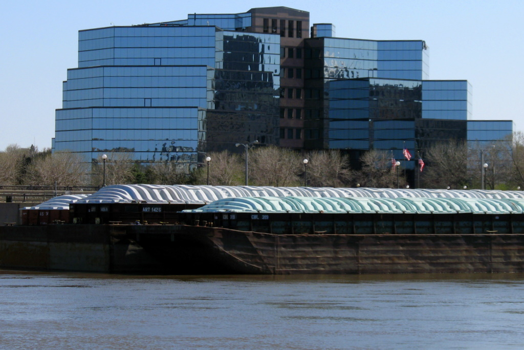 all glass building with a Mississippi River barge parked in front of it