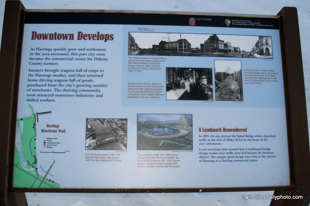 A landmark sign shows a couple of historical photos of the original downtown and the spiral bridge before it was torn down with the new bridge in place.