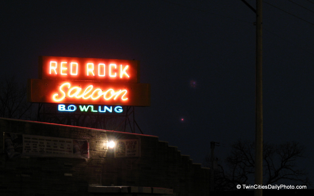 The neon business sign of the Red Rock saloon in Newport, Minnesota is powered on at night.