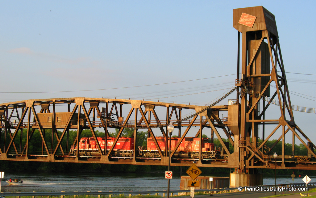 Two trains crossing the Mississippi River on the Milwaukee road bridge.